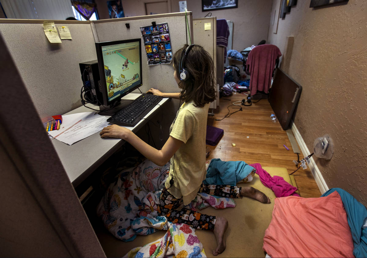 Aubrie Heenan, 17, left, plays Animal Crossing within her makeshift bedroom in a small office s ...
