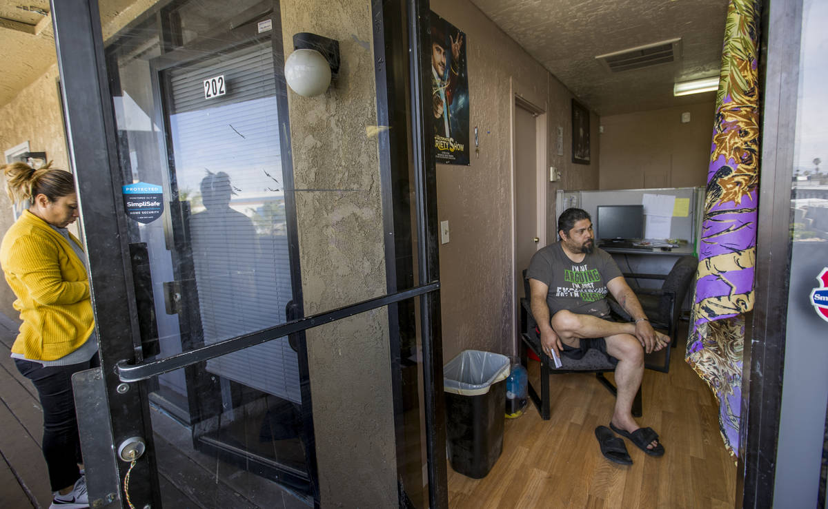 Jeremy Ferreira, right, sits a small office space he and his family of five are temporarily liv ...
