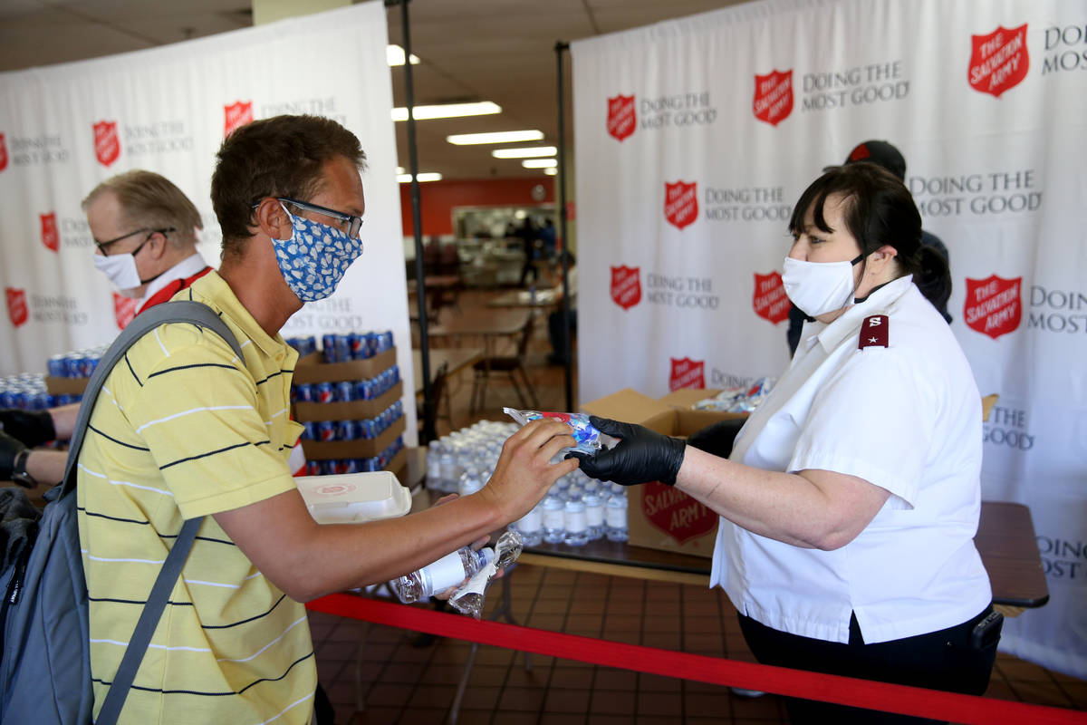 The Salvation Army Lieutenant Heather Baze gives a pandemic kit to Jose Gonzalez in North Las V ...