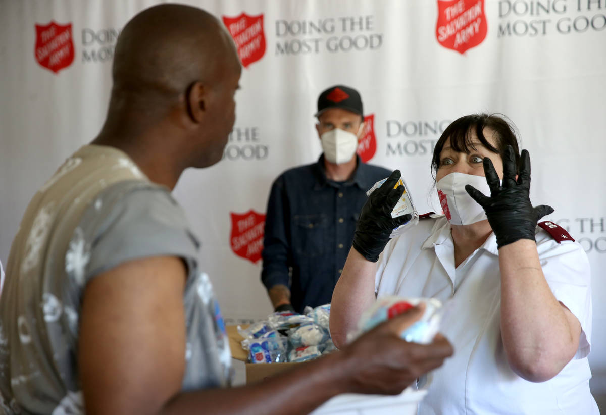 The Salvation Army Lieutenant Heather Baze gives a pandemic kit to Demarlo Donahue, 46, in Nort ...