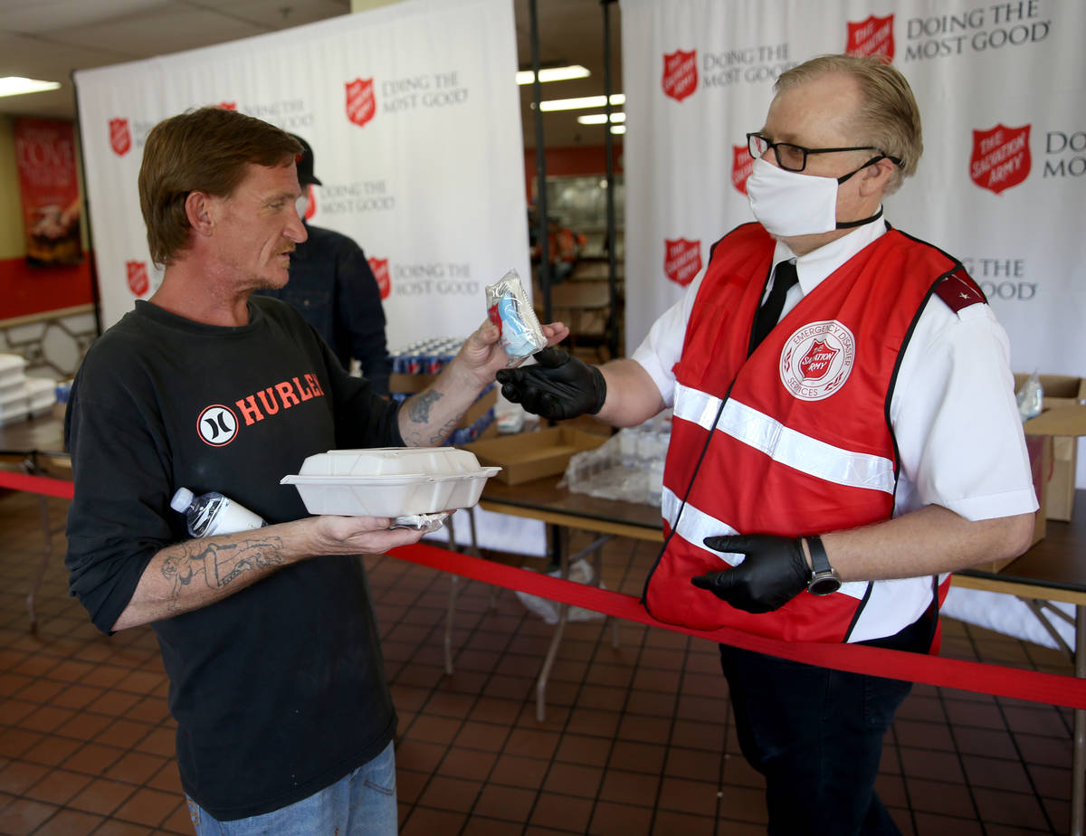 The Salvation Army Lieutenant Ty Baze gives a pandemic kit to Dale Davis, 42, in North Las Vega ...