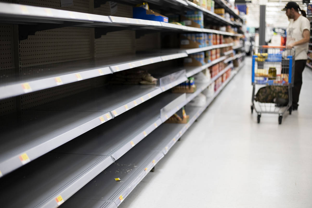 The rice and beans sections at Walmart are almost empty as Todd Holmgren shops for groceries on ...