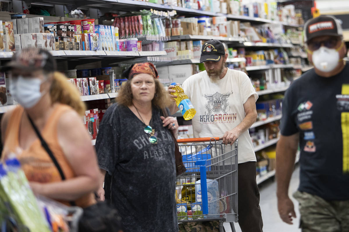 Debbie Holmgren and Todd Henke, flanked by two masked shoppers, pick up groceries at Walmart on ...