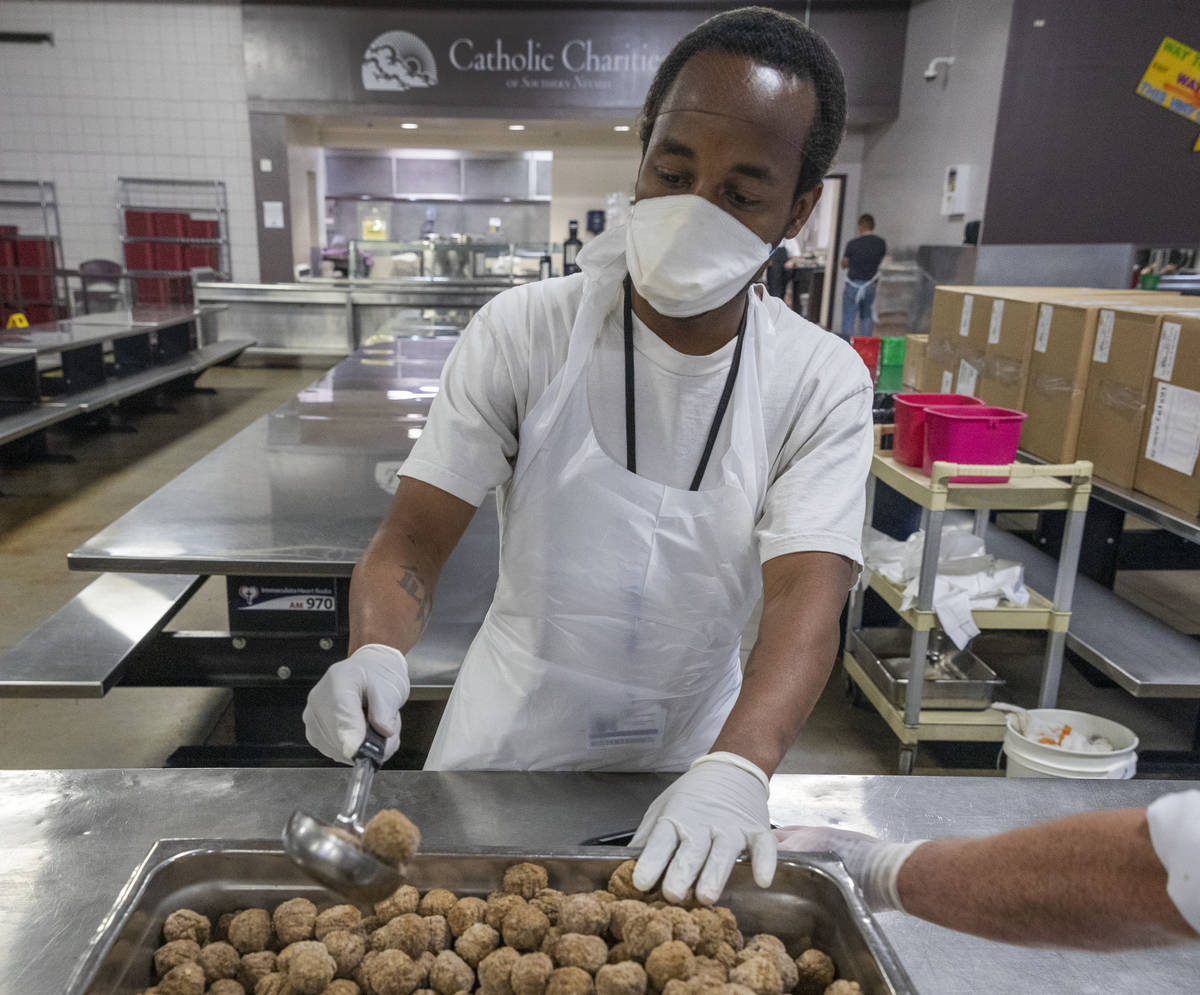 Kevin Terry helps package a dish for Meals on Wheels, at Catholic Charities of Southern Nevada ...