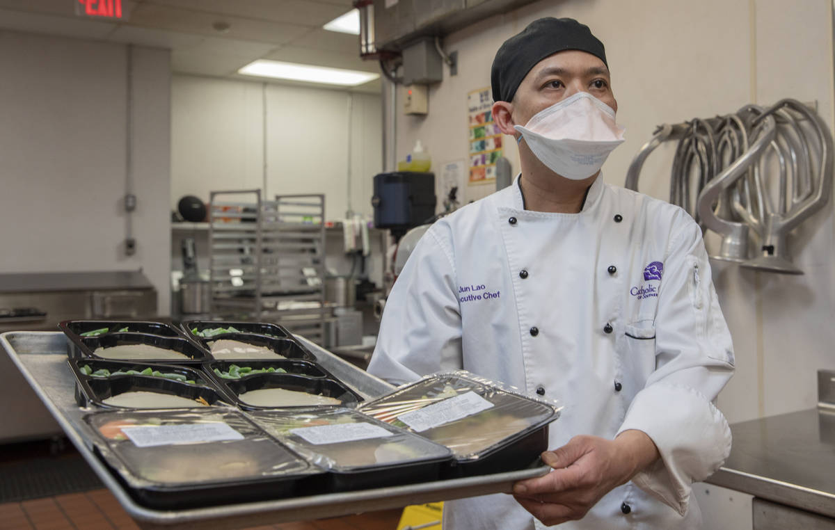Catholic Charities of Southern Nevada's executive chef Jun Lao carries different dishes to be d ...