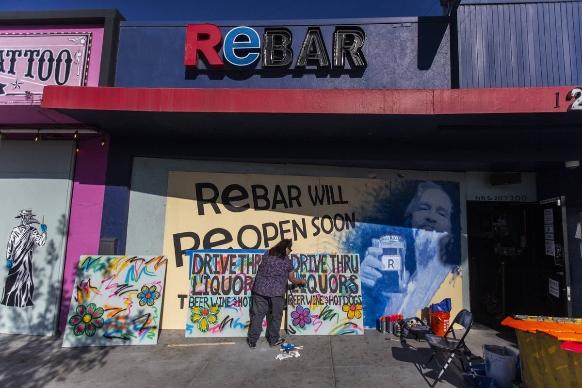 Geneva Marquez paints signage at ReBAR in the Arts District on Saturday, April 4, 2020, in Las ...