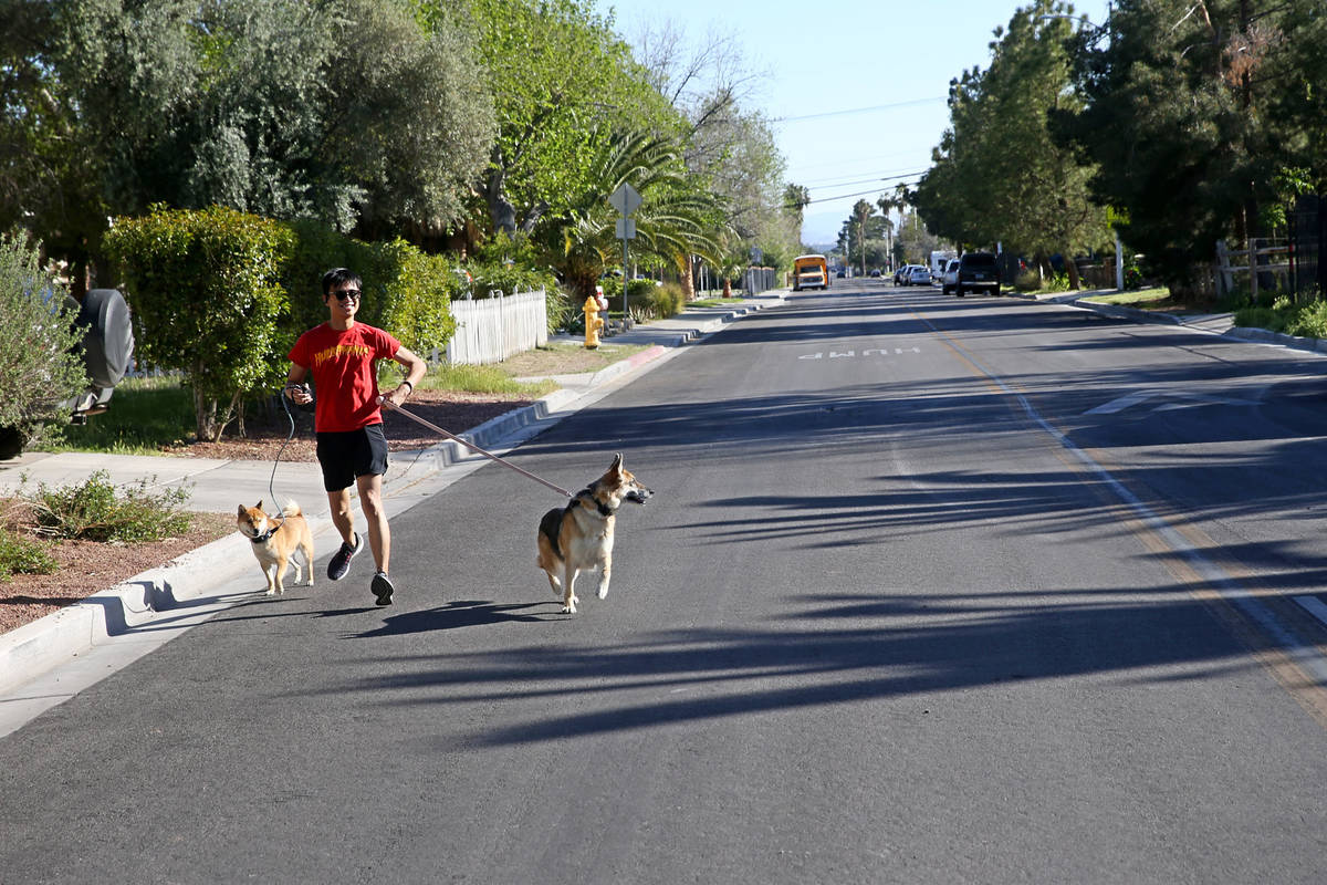 Joaquin Poblete of Las Vegas exercises with his dogs on 6th Street in the John S. Park neighbor ...