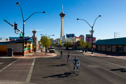 People bike down Main Street in the Arts District as traffic remains light in the wake of the c ...