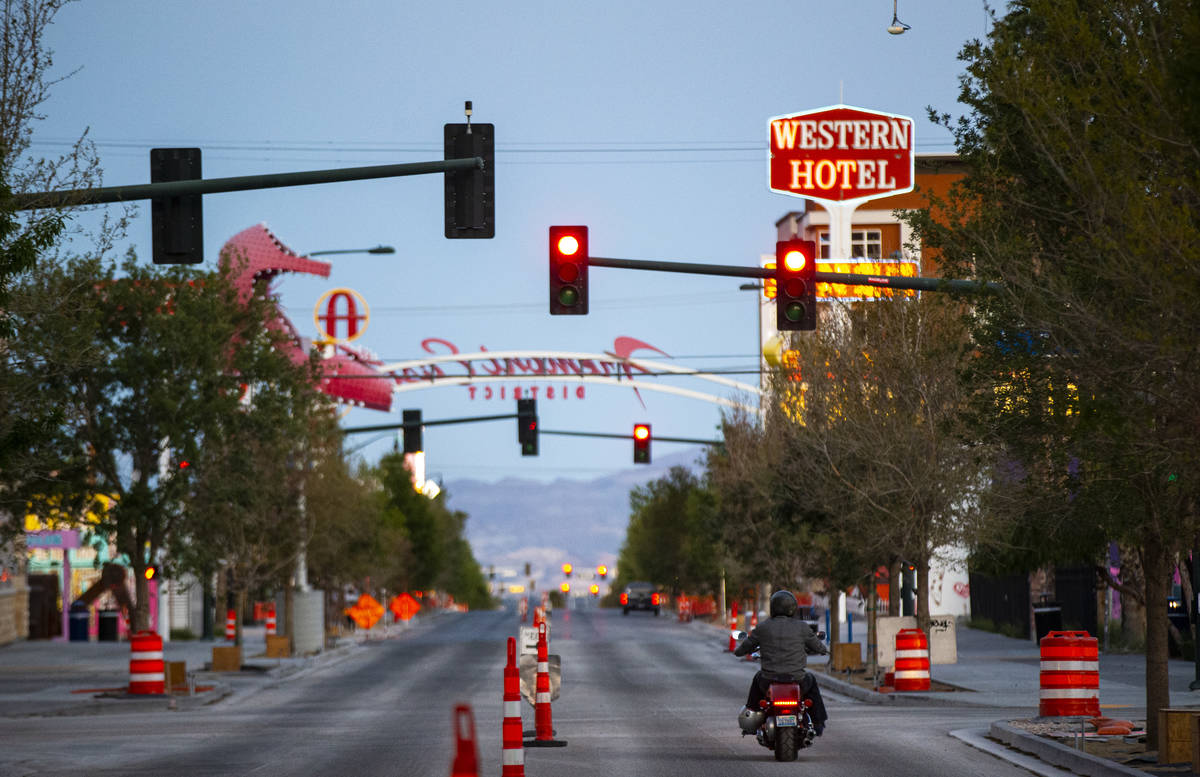 A man rides a motorcycle down Fremont Street as traffic remains light in the wake of the closur ...