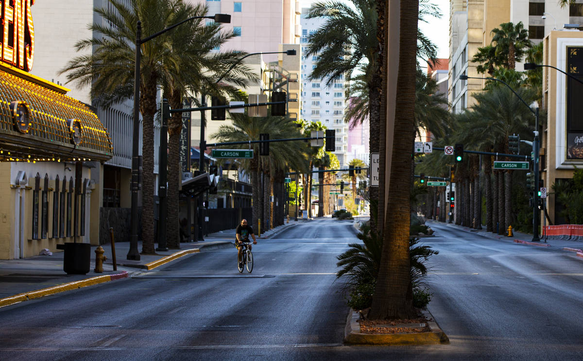 A man rides a bike down Casino Center Boulevard near Fremont Street as traffic remains light in ...
