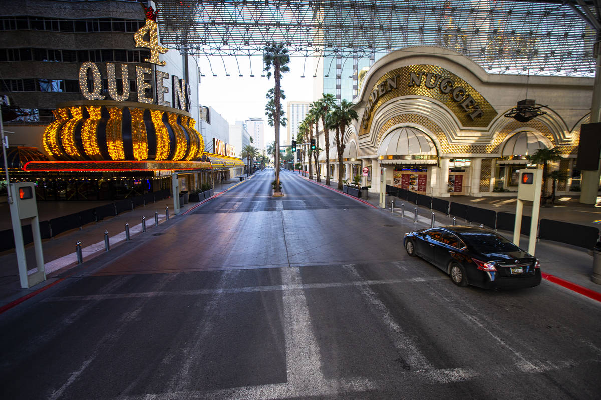 A car drives down Casino Center Boulevard near Fremont Street as traffic remains light in the w ...