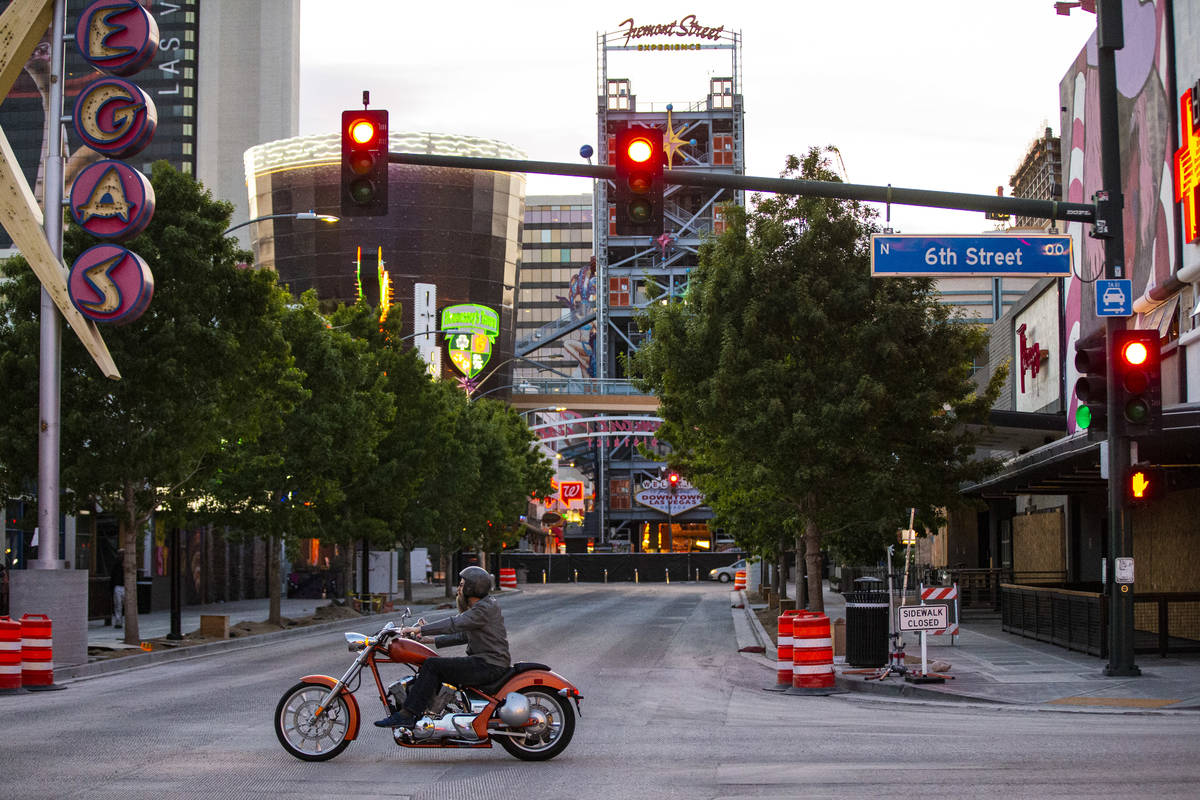 A man rides a motorcycle along 6th Street past Fremont Street as traffic remains light in the w ...