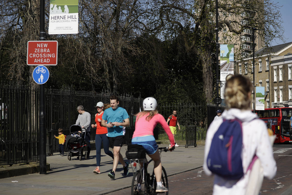People observe social distancing as they pass by the locked gates to Brockwell Park in London, ...