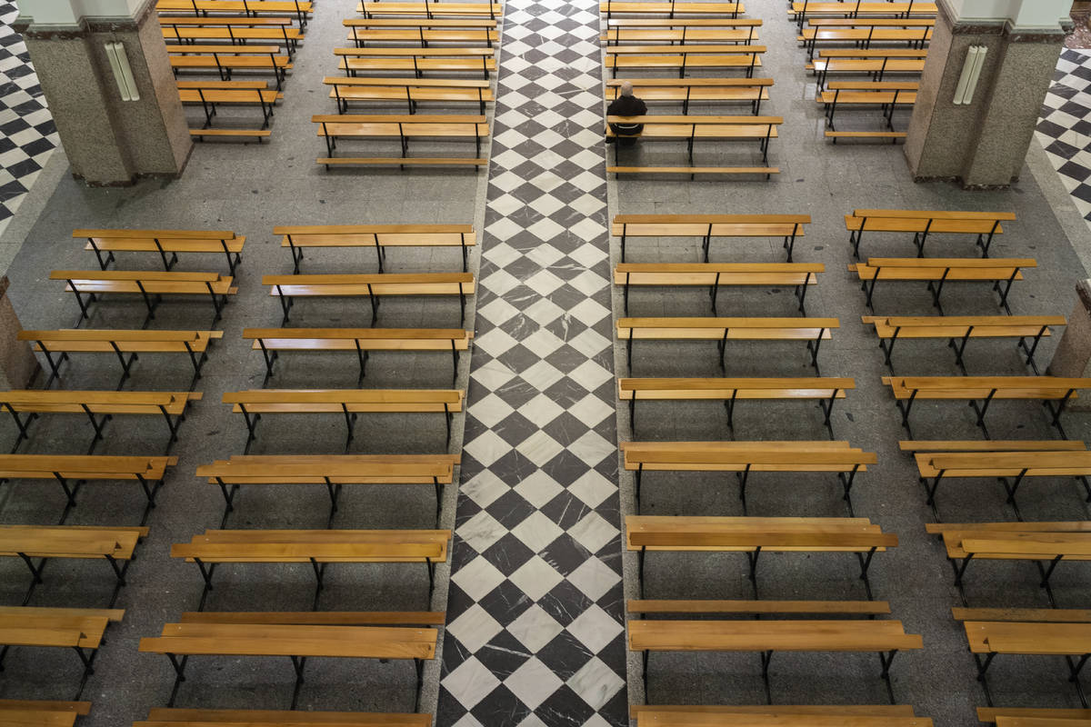 A Catholic priest sits on an empty bench due to social distancing guidelines during the coronav ...