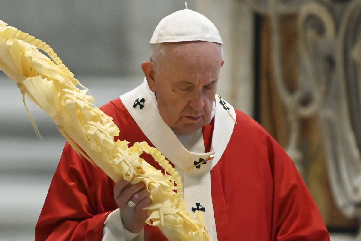 Pope Francis holds a palm branch as he celebrates Palm Sunday Mass behind closed doors in St. P ...