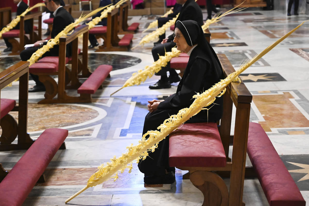 A nun sitting by a palm branch attends the Pope's Palm Sunday Mass behind closed doors in St. P ...