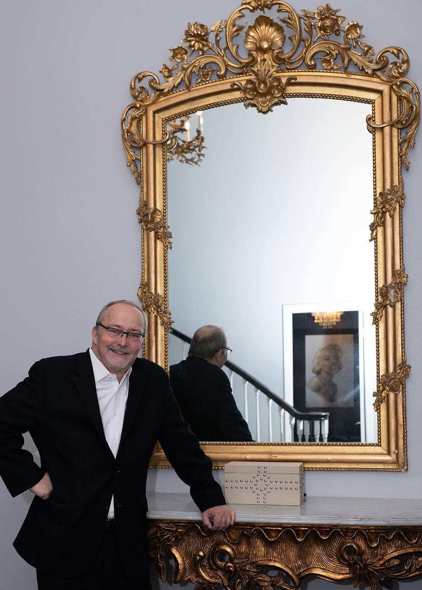 Myron Martin leans against an ornate entry table topped with a gilt-framed mirror, some of the ...