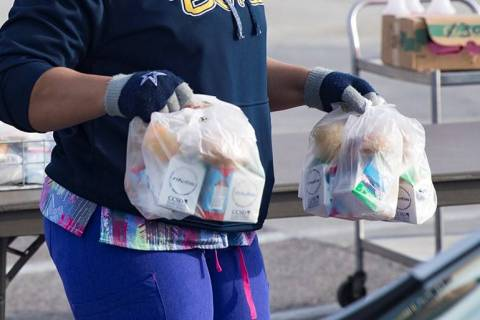 A worker hands out breakfast and lunch packages to families at a school in March 2020. (Rachel ...