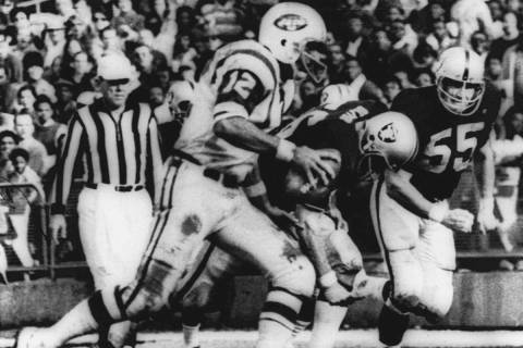 New York Jets' quarterback Joe Namath (12) sweeps around the right side past Oakland defenders ...