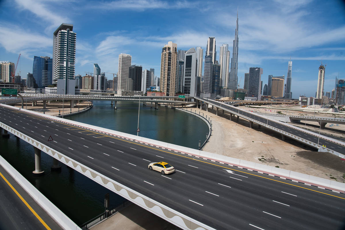 A lone taxi cab drives over a typically gridlocked highway with the Burj Khalifa, the world's t ...