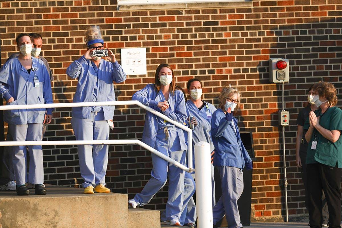 Hospital workers appear at a staff entrance as motorcyclists and friends of Chad Edmonds, of Ce ...