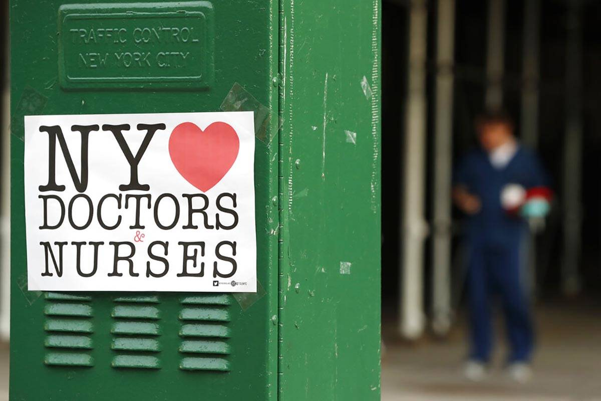A sign acknowledging the work of doctors and nurses is posted on a traffic control box outside ...