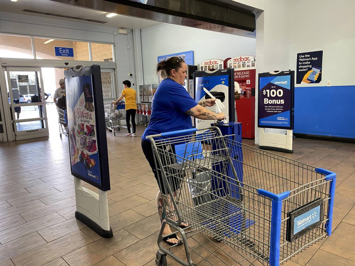 Customers grab sanitizing wipes at Walmart Supercenter at 3950 W. Lake Mead Blvd. in North Las ...