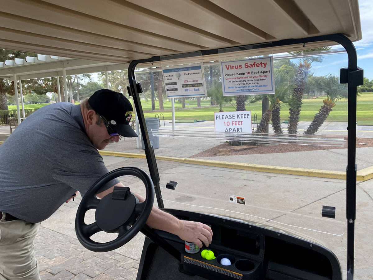 Timothy Metcalf of Las Vegas prepares for a round of golf among social distancing signs at Las ...
