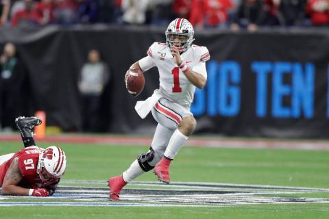 Ohio State quarterback Justin Fields (1) runs with the ball past Wisconsin defensive end Isaiah ...