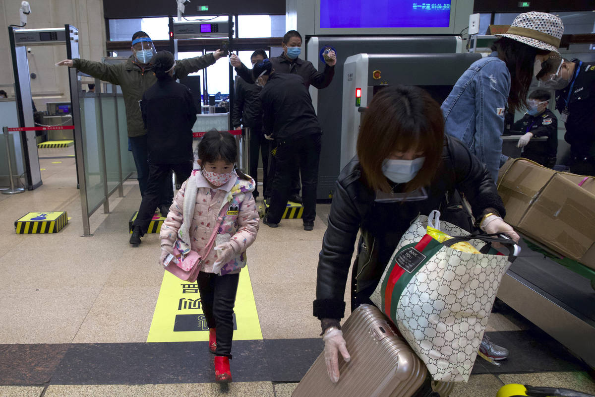 Passengers wearing face masks to protect against the spread of new coronavirus pass through sec ...