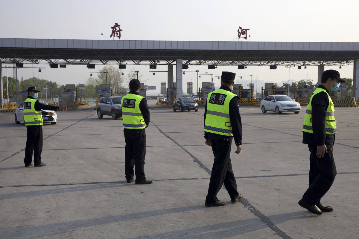 Security personnel wearing face masks to protect against the spread of new coronavirus direct v ...