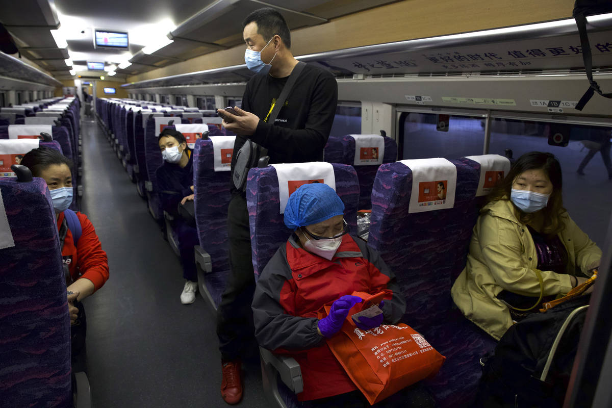 Passengers wearing face masks to protect against the spread of new coronavirus board the first ...
