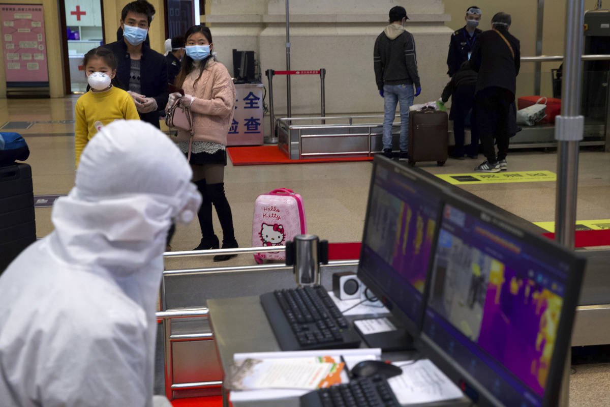 Passengers wearing face masks to protect against the spread of new coronavirus watch as a worke ...
