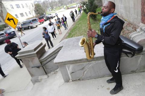 Olu Sijuwade, of Milwaukee, plays a tenor saxophone for those waiting in line to vote at Rivers ...