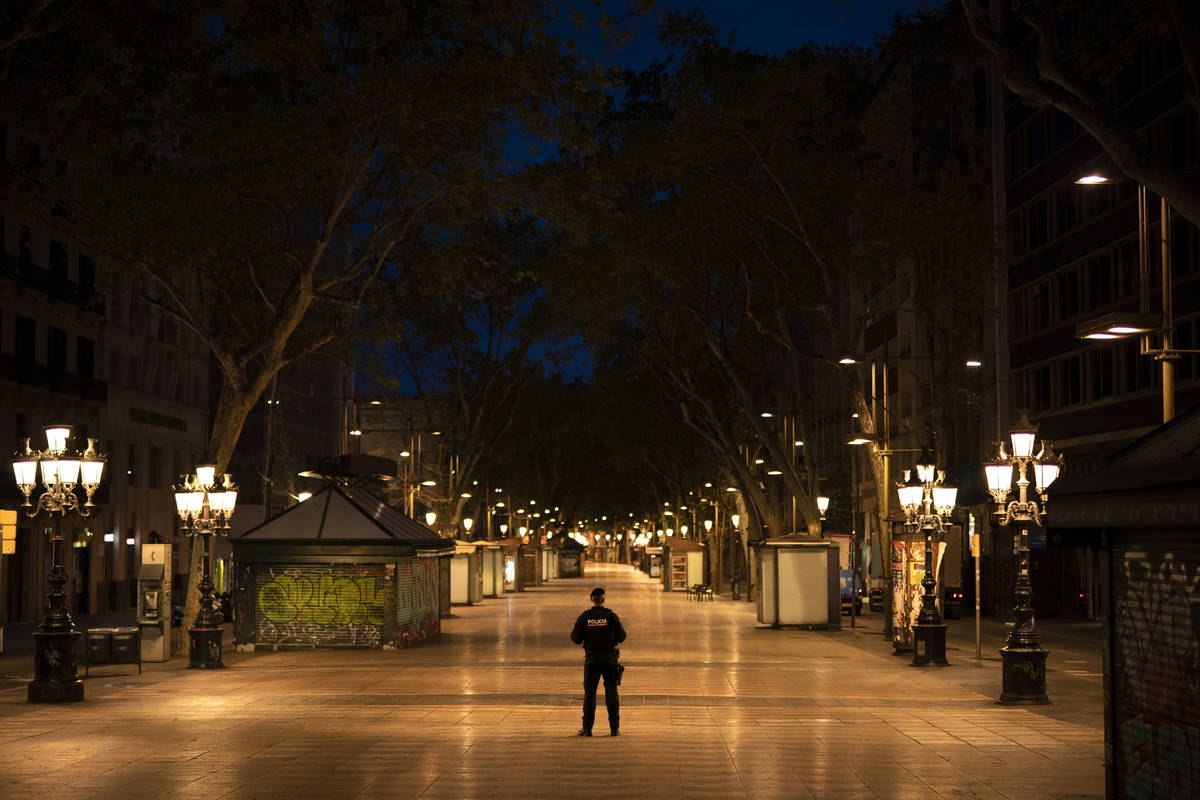 A Catalan police officer stands in the middle of La Ramblas street devoid of the usual crowds d ...