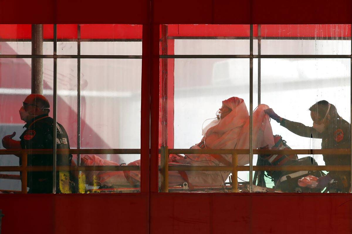 Emergency medical technicians wheel a patient into Elmhurst Hospital Center's emergency room, T ...