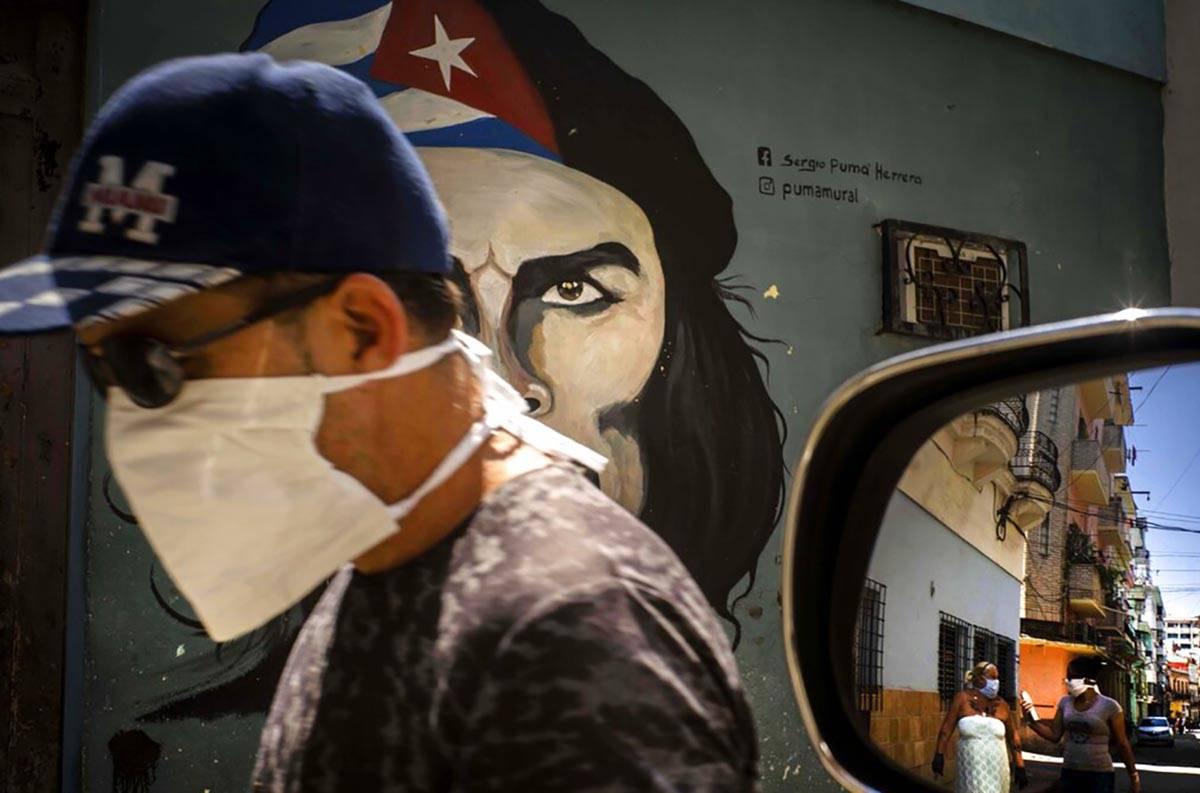 "A man wearing a mask walks alongside a mural of Ernesto ""Che"" Guevara as other pedest ..."