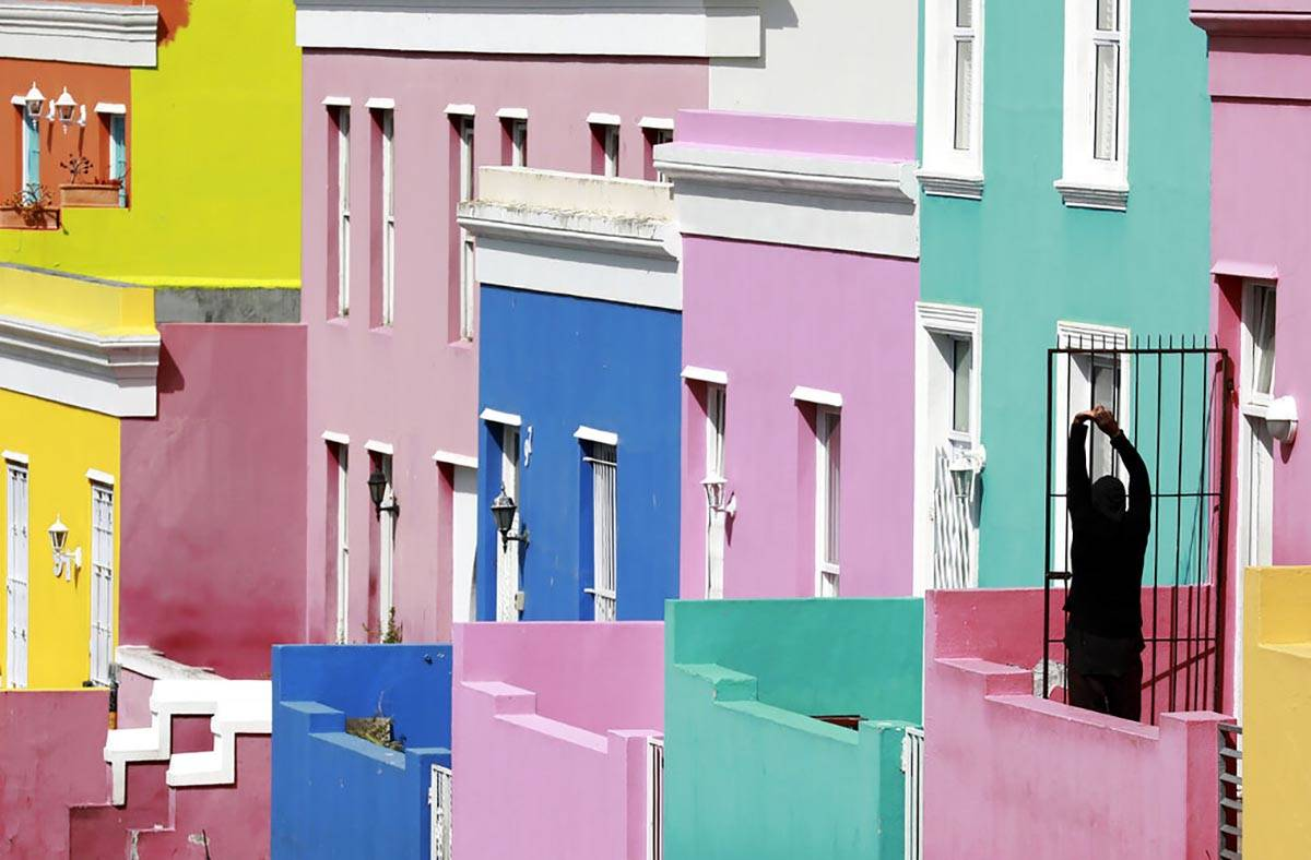 A man stretches, at the entrance of his home in Bo-Kaap, Cape Town, South Africa, Tuesday, Apri ...