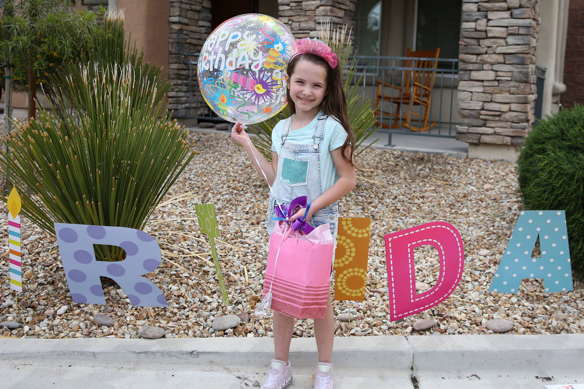 Tenley Hynds, 8, poses for a photo after receiving her birthday present after a drive by birthd ...