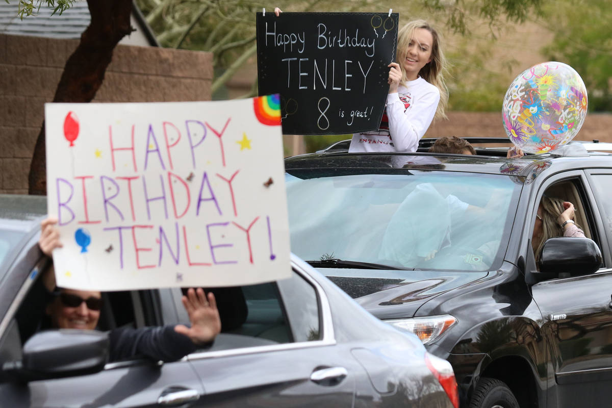 Amanda Grange, left, and Aba Rogers, 16, top right, hold birthday signs who came to celebrate T ...