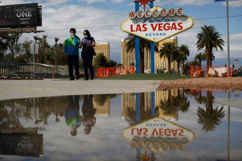 "People wearing face masks visit the usually crowded ""Welcome to Fabulous Las Vegas Nevada& ..."