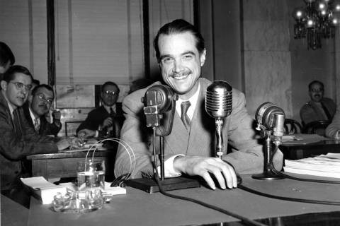 In this Nov. 15, 1947, file photo, Howard Hughes smiles as he sits in the witness chair before ...