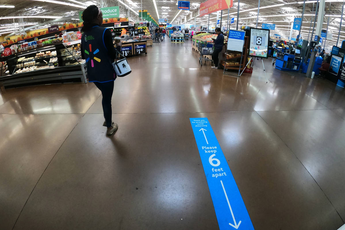 A sign at the entrance of Walmart Supercenter, 3950 W. Lake Mead Blvd., tells people to practic ...