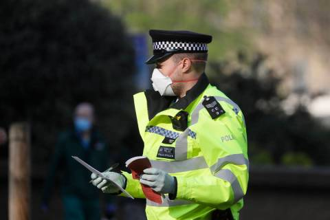 A British police officer wears a 3M face mask, with few police officers in Britain seen wearing ...