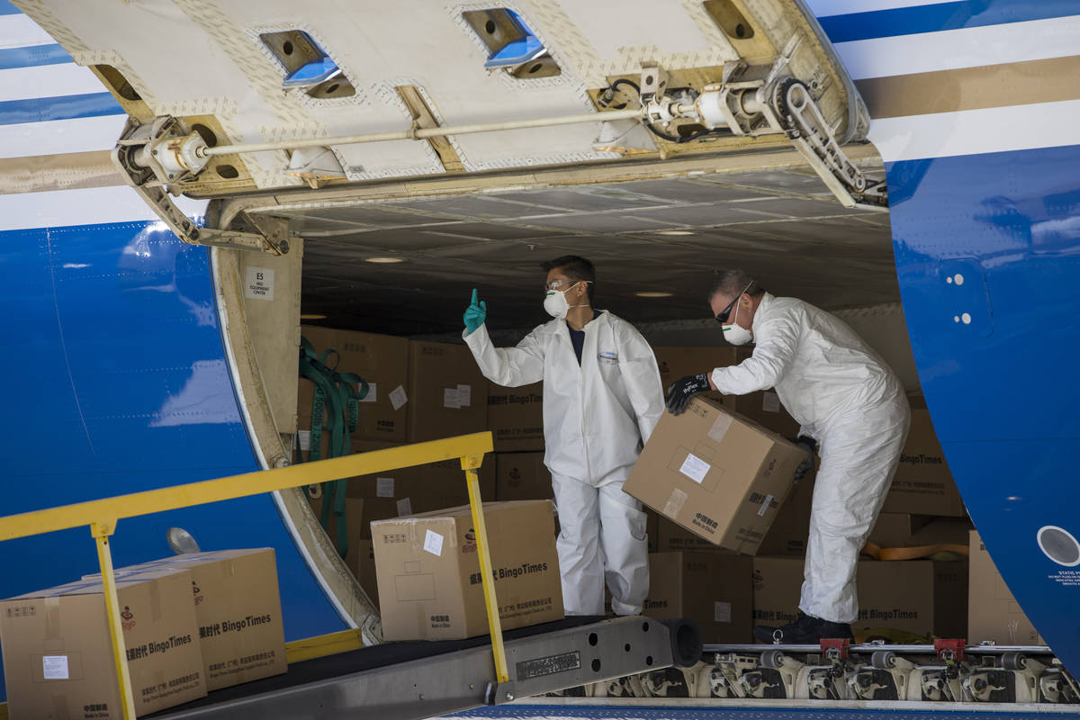 Transport workers unload some of the 1 million surgical masks arriving from Guangzhou, China, a ...