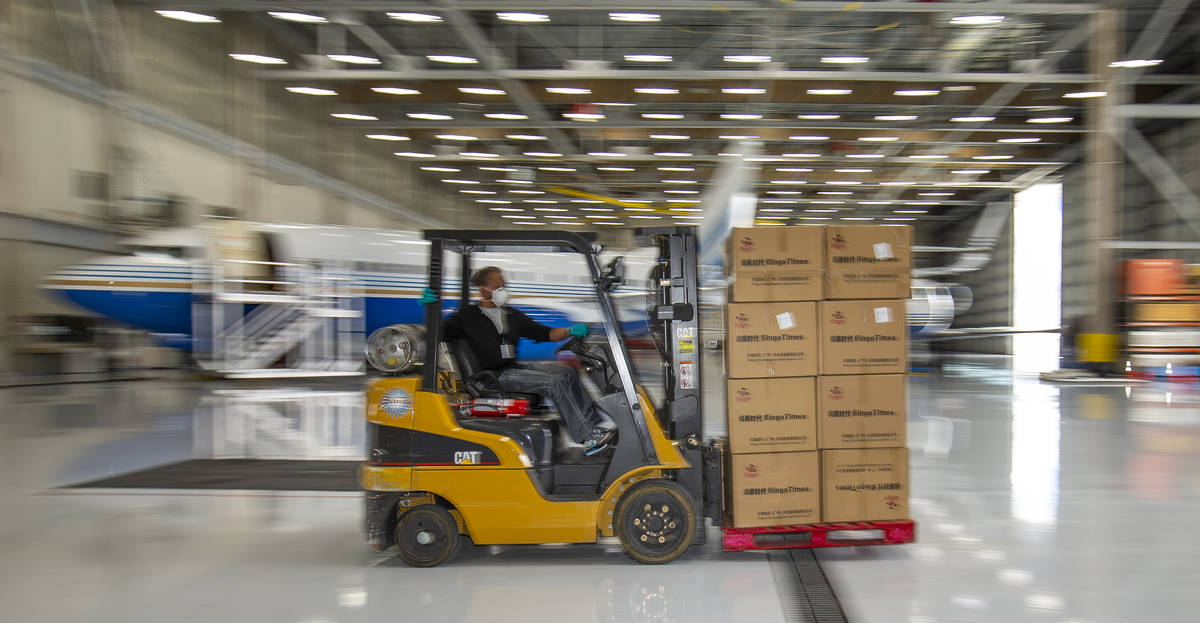 A transport worker moves some of the 1 million surgical masks arriving from Guangzhou, China, a ...