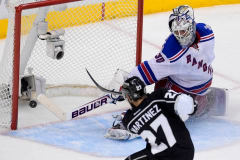 Los Angeles Kings defenseman Alec Martinez, left, scores the winning goal past New York Rangers ...