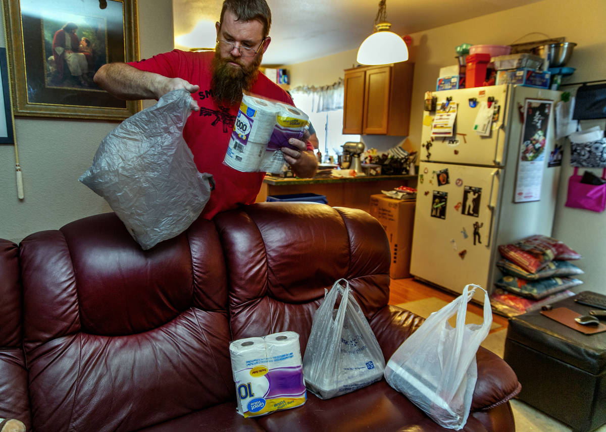 Marty Coon separates items for his wife Veronica who prepares for another donation drop with th ...