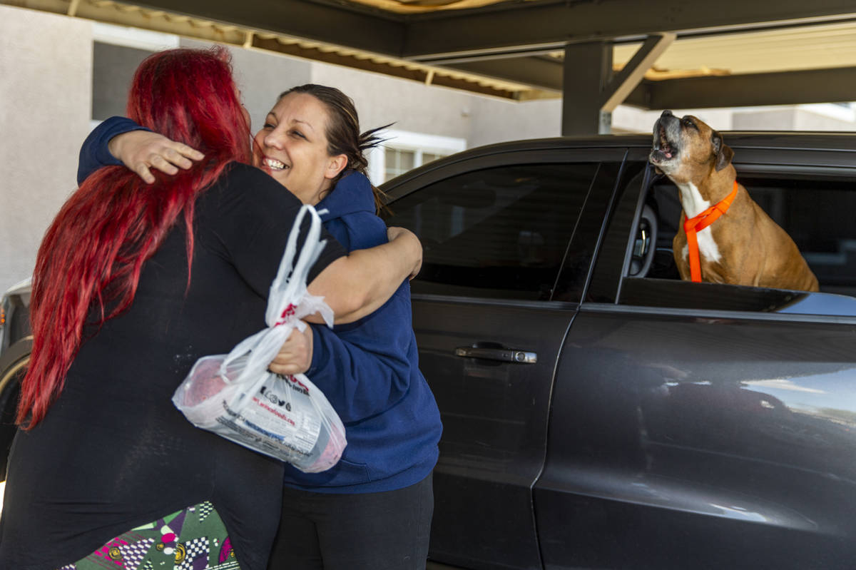 Veronica Coon delivers ground beef to Heather Born as her dog Chase barks during another supply ...