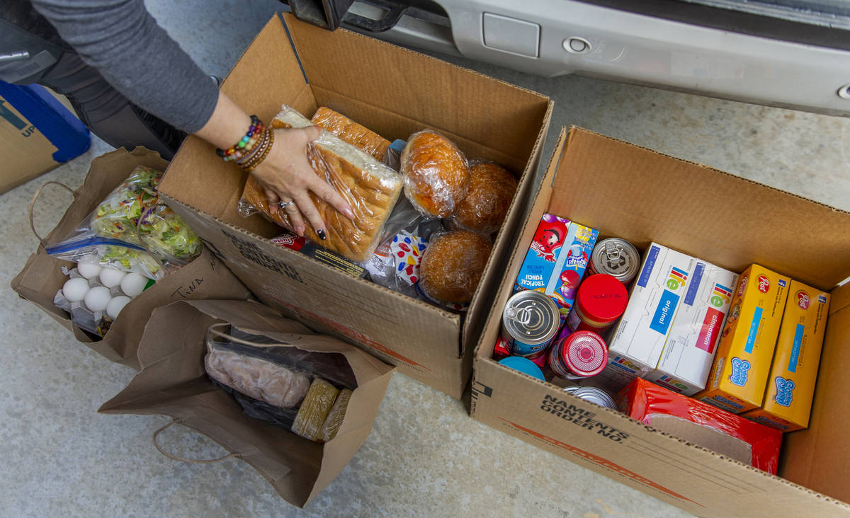 Kat Morris divides up food and supplies for another donation drop with the COVID-19 Barter Grou ...